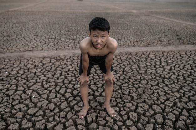 O menino de pé curvado e mão pega joelhos, aquecimento global e crise da água Foto gratuita