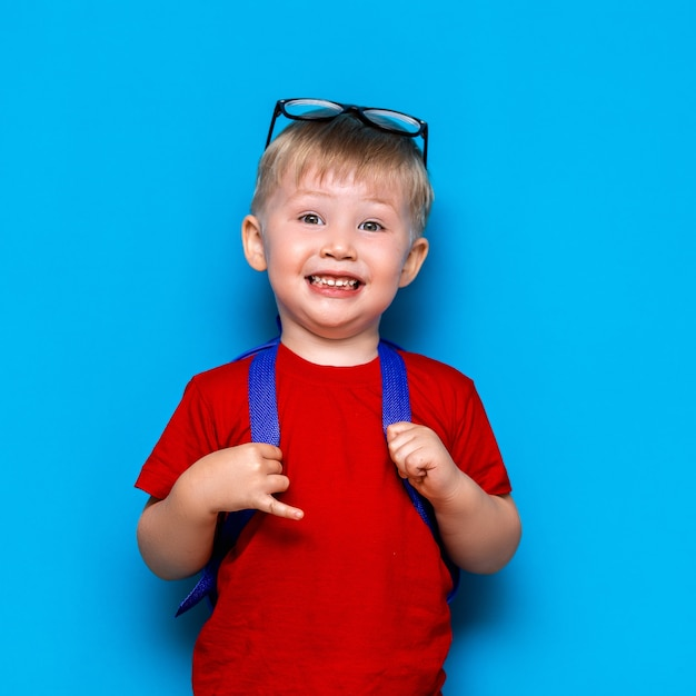 O menino de sorriso feliz no t-shirt vermelho com vidros em sua cabeça está indo à escola pela primeira vez. criança com bolsa escola. criança Foto Premium