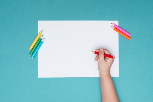 O menino desenha em uma folha de papel branca Foto Premium