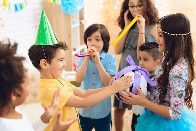 O menino do feliz aniversario recebe a bola do futebol como o presente de aniversário. Foto Premium