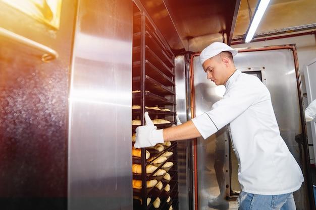 O menino do padeiro introduz um carro com bandejas de cozimento cruas da massa em um forno industrial em uma padaria. Foto Premium