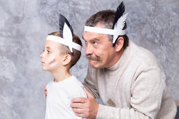 O menino e o avô jogam índios em uma parede de parede cinza. neto e neto sênior jogar injun Foto Premium