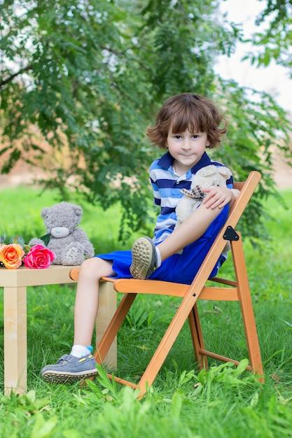 O menino em uma t-shirt azul listrada senta-se em um banquinho ao ar livre entre os verdes Foto Premium