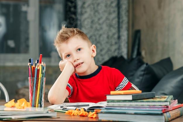 O menino está triste, entediado de fazer a lição de casa. Foto Premium