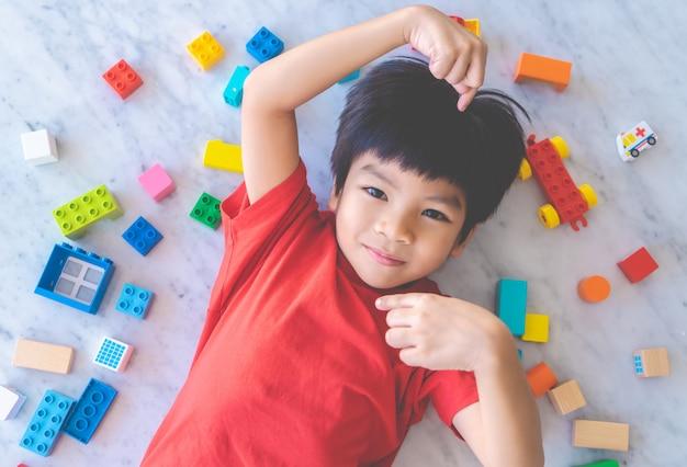 O menino feliz cercado pelo brinquedo colorido obstrui a vista superior. Foto Premium