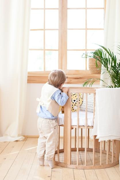 O menino fica ao lado do berço no quarto e espia. bebê solitário está no jardim de infância perto do berço. solidão. decoração de quarto infantil ecológico em estilo escandinavo. o garoto está em casa. Foto Premium