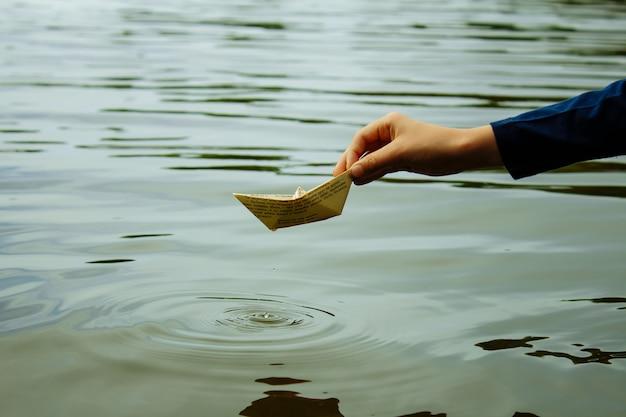 O menino lança um barco em um close de água Foto Premium