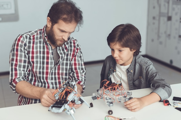 O menino olha com cuidado enquanto um homem recolhe um robô Foto Premium
