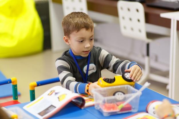 O menino recolhe um modelo de um carro controlado por rádio Foto Premium