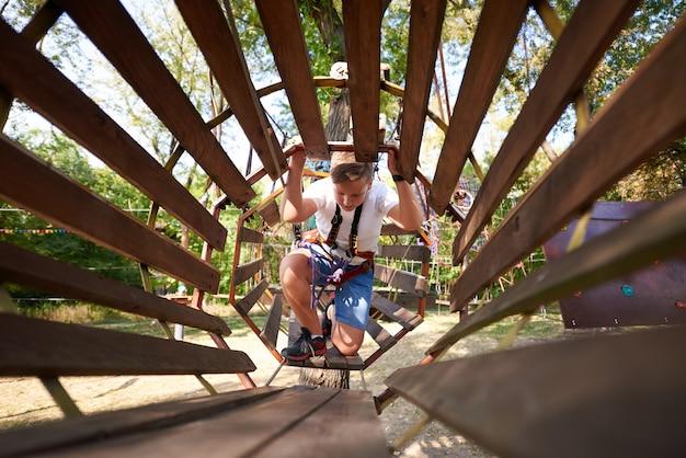 O menino supera o obstáculo no parque de cordas. Foto Premium