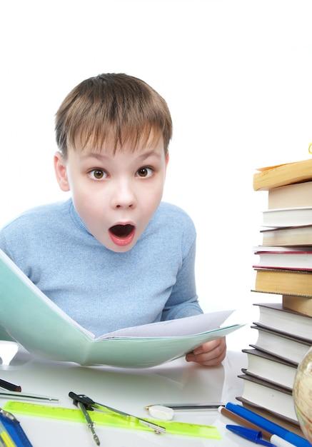 O menino surpreendeu atrás de uma mesa com livros Foto Premium