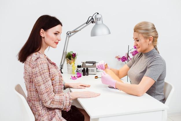O mestre de manicure abre um novo conjunto de ferramentas para o cliente Foto Premium