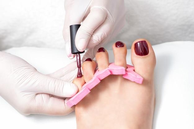 O mestre de manicure está pintando nas unhas dos pés femininos com esmalte marrom com pincel e usando luvas brancas Foto Premium