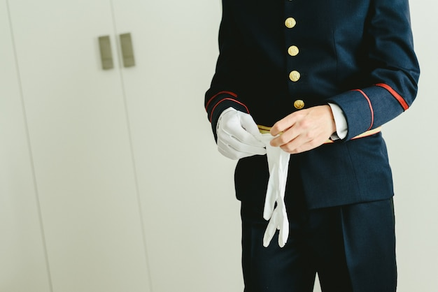 O militar entrega as mãos que põem sobre algumas luvas brancas elegantes. Foto Premium