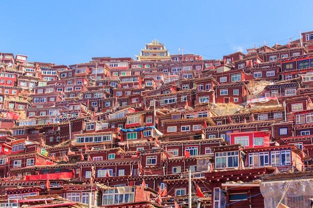 O monastério e a casa vermelhos em larung gar (academia budista) no dia e no fundo do sol são céu azul, china Foto Premium