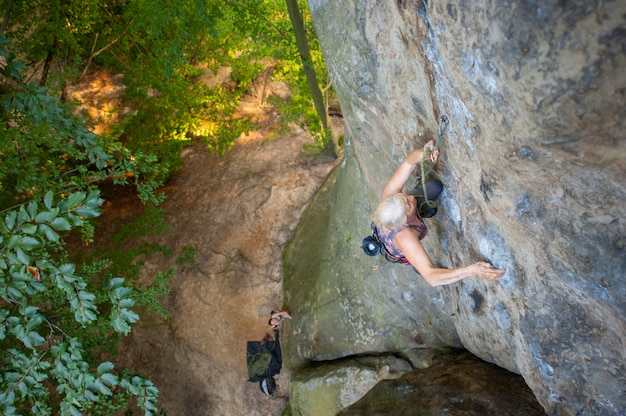 O montanhista de rocha da mulher mais idosa está escalando com carabinas e corda em uma parede rochosa da rocha grande. Foto Premium