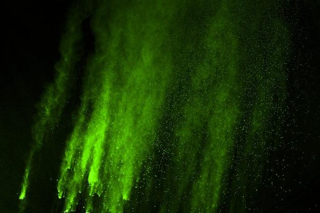 O movimento da explosão de poeira abstrata congelou o verde no fundo preto. Foto Premium
