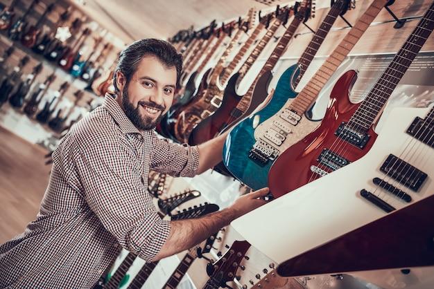 O músico farpado adulto compra a guitarra elétrica na loja da música. Foto Premium