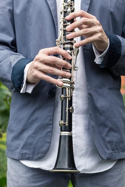 O músico segura um clarinete nas mãos. Foto Premium