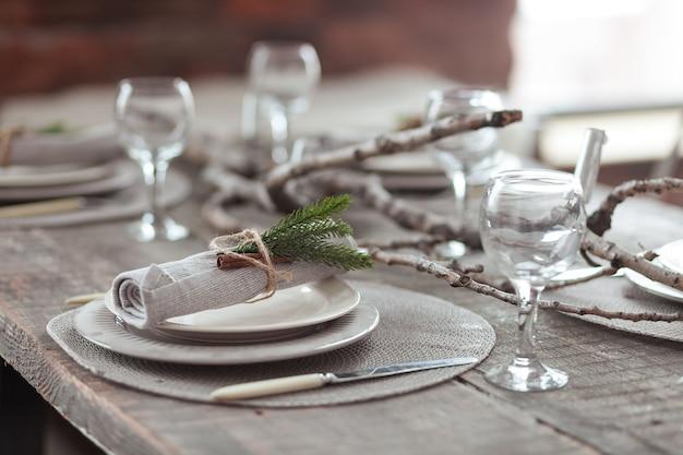 O natal rústico serviu a tabela de madeira com pratas do vintage, velas e galhos do abeto. Foto gratuita