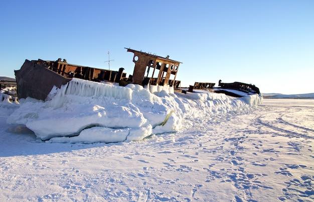 O navio oxidado velho abandonado que coloca na costa do lago congelado. baikal, rússia Foto Premium