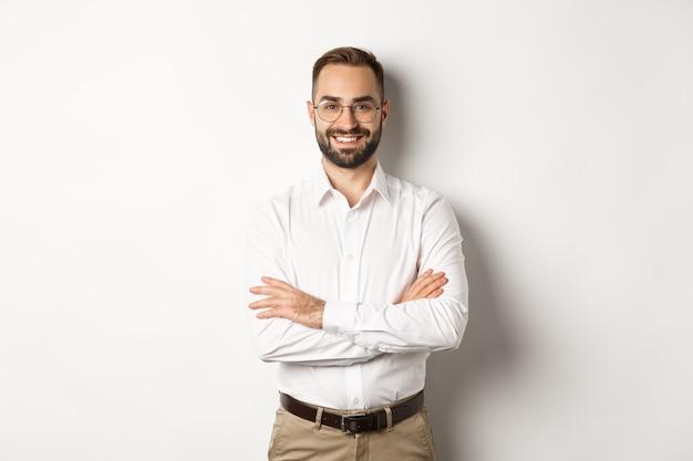 O negócio. jovem empresário profissional de óculos, sorrindo para a câmera, cruze o braço no peito com Foto gratuita