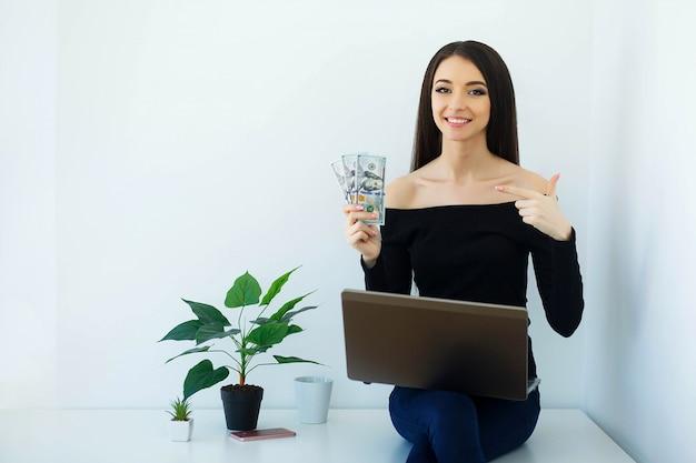 O negócio. mulher de negócios linda segurando nas mãos de dinheiro. senta-se em cima da mesa no escritório big light e trabalha no computador. garota feliz trabalha em casa. alta resolução Foto Premium