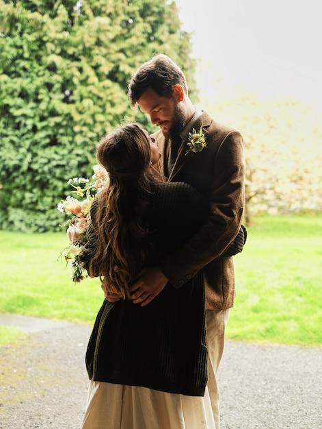 O noivo abraça a noiva em um dia nublado, amor, beijo e ternura nos braços Foto Premium