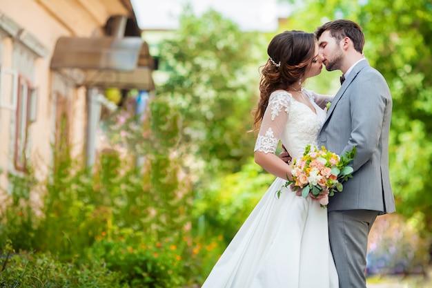 O noivo e a noiva com buquê fica no parque Foto Premium