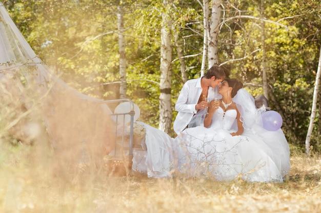 O noivo e a noiva na floresta em uma cama Foto Premium