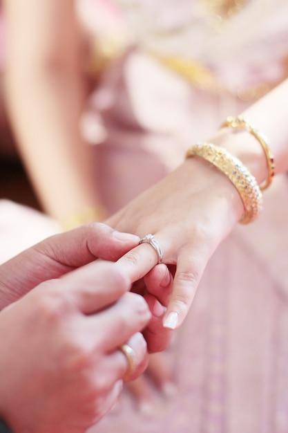O noivo entrega guardar as mãos da noiva com aliança de casamento na cerimônia de casamento tailandesa tradicional. Foto Premium