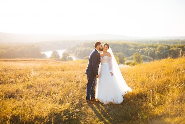 O noivo está beijando sua noiva em uma bochecha e ela está sorrindo. eles estão de pé em uma paisagem banhada pelo sol. Foto Premium