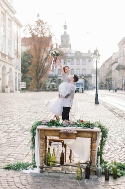 O noivo segura a noiva nos braços e fica no contexto de prédios antigos da cidade. Foto Premium