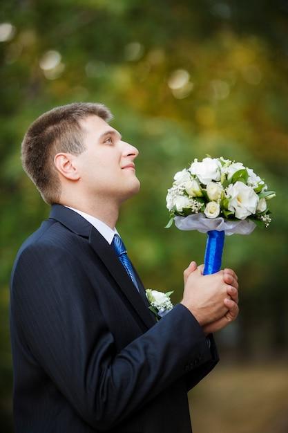O noivo tem um buquê de noiva de casamento na mão e olha para cima Foto Premium