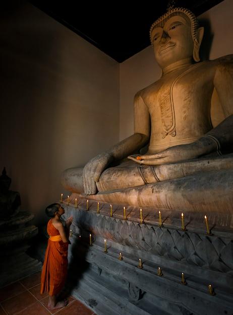 O novato está olhando para a grande imagem de buda na igreja para orar pelo respeito à religião. Foto Premium