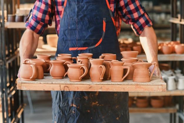 O oleiro masculino entrega guardar a bandeja com os potenciômetros cerâmicos cozidos na cerâmica. Foto Premium