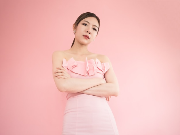 O olhar asiático da mulher para baixo e o braço cruzam, mulheres bonitas que levantam no fundo cor-de-rosa. Foto Premium