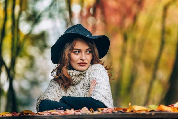 O olhar de uma bela dama de chapéu preto é direcionado para o lado. Foto Premium
