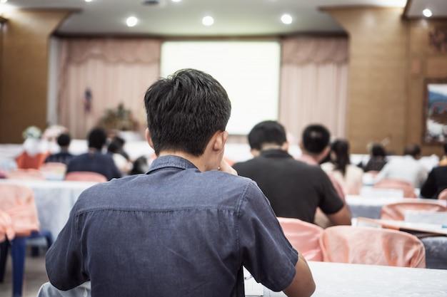 O orador no palco, a audiência de visão traseira escuta um conferencista de discurso em uma sala de conferências ou uma reunião de seminário Foto Premium