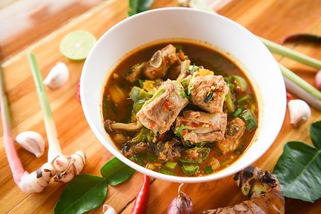 O osso picante da carne de porco da sopa do caril do reforço de carne de porco com a bacia de sopa quente e ácida com os vegetais frescos tom yum de tom yum e tempera ingredientes. Foto Premium