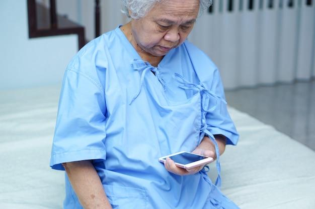 O paciente asiático da mulher idosa ou idosa da senhora idosa leu o email no telefone celular. Foto Premium
