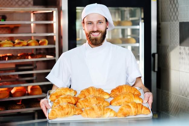 O padeiro masculino considerável guarda uma bandeja com croissant franceses na frente de uma padaria e sorri. Foto Premium