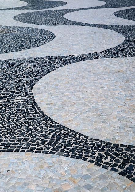 O padrão de ondas do pavimento português na praia de copacabana no rio de janeiro, brasil Foto Premium