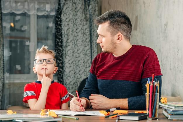 O pai ajuda o filho a fazer a lição de casa na escola. Foto Premium