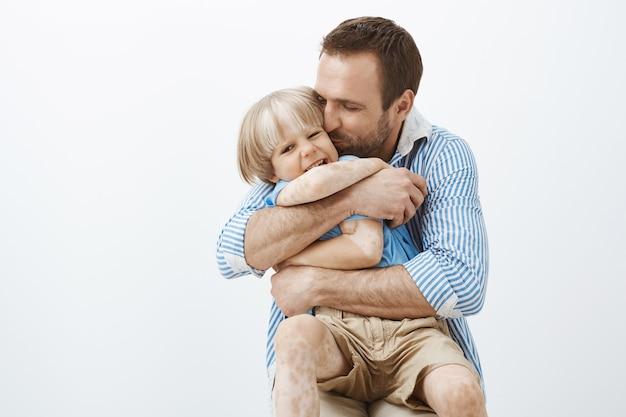 O pai ama seu filho como ninguém. pai carinhoso e bonito, abraçando e beijando a criança na bochecha, feliz por estar com a criança, em pé sobre a parede cinza Foto gratuita