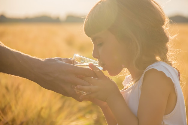 O pai dá à criança um copo de água. foco seletivo. Foto Premium
