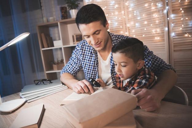 O pai e o filho estão lendo o livro com a lente de aumento na tabela. Foto Premium