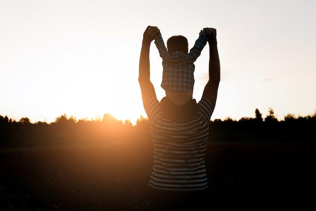 O pai e o filho que andam no campo no tempo do por do sol, menino que senta-se em equipa os ombros. Foto gratuita
