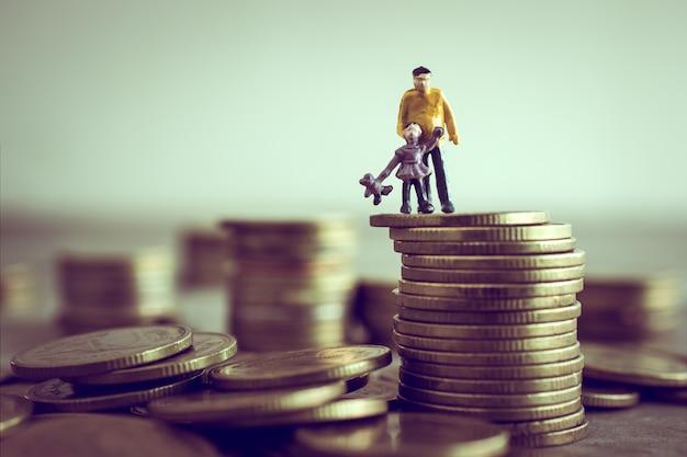 O pai e os filhos diminutos que estão em cima do dinheiro salvar o conceito do dinheiro. Foto Premium