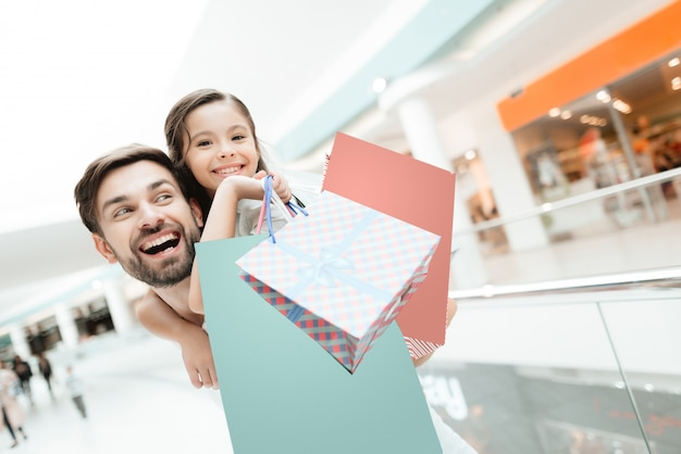 O pai leva a filha sobre para trás no shopping. Foto Premium